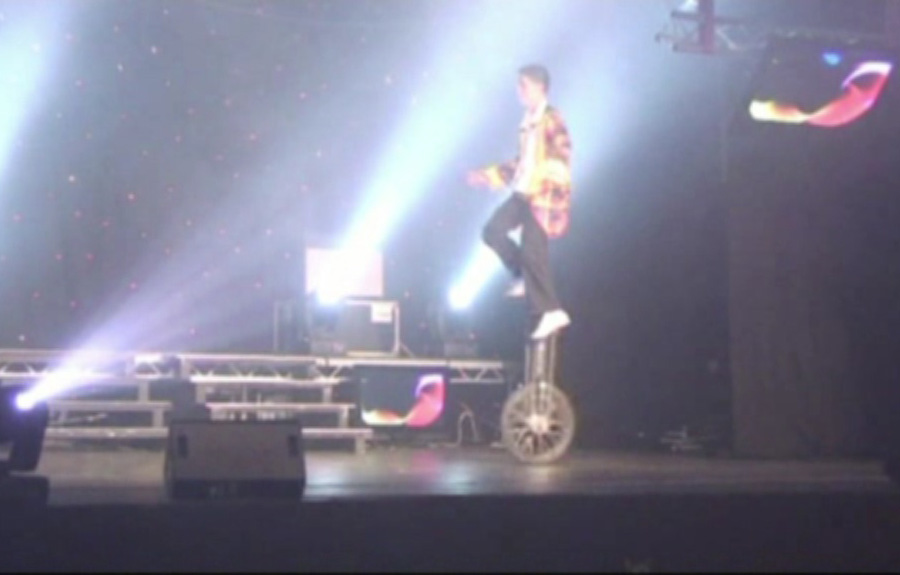 Riding-a-giraffe-unicycle-at-youth-talent-show-with-TK-Arts