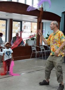 Tom-TK-Arts-demonstrates-scarf-juggling-at-community-event-for-families