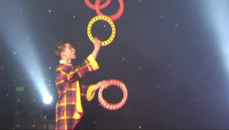 Young-person-juggles-with-4-rings-at-talent-show-with-TK-Arts